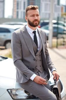 かっこいいひげを生やしたビジネスマンは、代表的な車のボンネットに座っています
