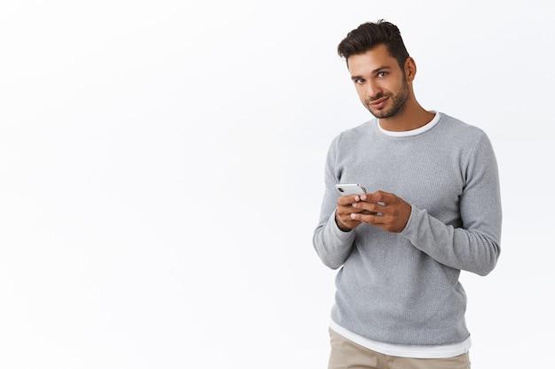 스마트폰을 들고 회색 스웨터를 입은 잘 생긴 수염 남자, 귀여운 미소로 카메라를 보고, 앱에서 채팅하고, 응용 프로그램을 사용하여, 흰색 벽