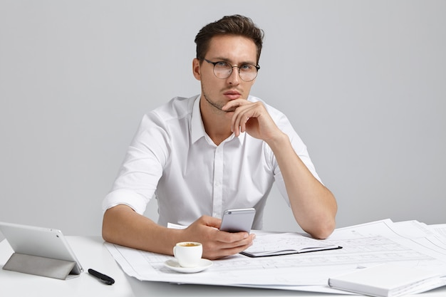 Good looking bearded male contractor sitting at desk in modern office interior using mobile phone while studying blueprint, having thoughtful serious look, touching chin. people, job and occupation
