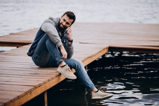 Good looking bearded man by the river in park sitting on dock