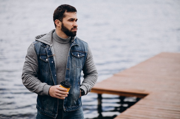 Good looking bearded man drinking coffee by the river in park