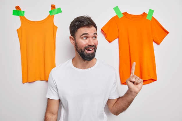 Tシャツを着た格好良いあごひげを生やした男性は、洋服をぶら下げて販売するアイテムを推奨し、不要な衣類を集めてリサイクルしたり、白い壁に隔離して寄付したりすることをお勧めします