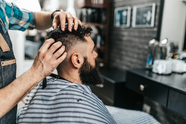 Good looking bearded man visiting hairstylist in barber shop.