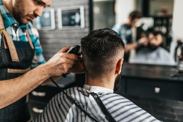 理髪店でヘアスタイリストを訪ねる格好良いひげを生やした男。