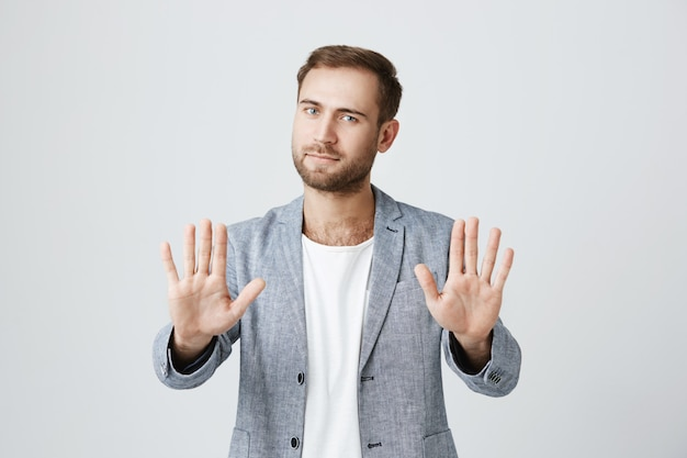 Good-looking bearded stylish man shows palms, say stop