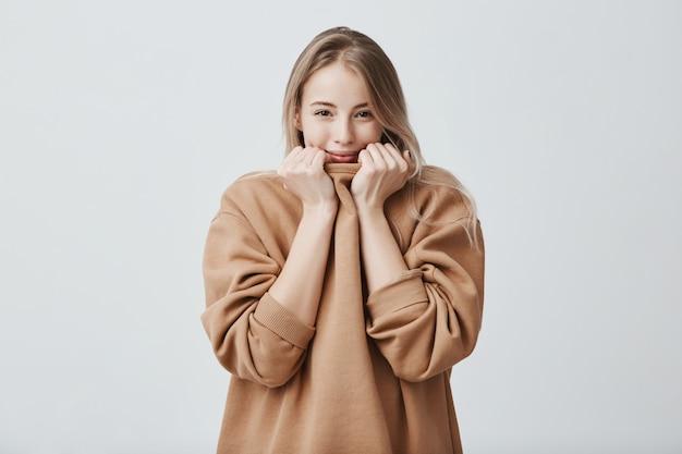 笑顔のイケメン美女、お世辞を聞いて嬉しい、孤立。きれいな髪と暗い魅力的な目で、セーターに顔を隠して恥ずかしがり屋のきれいな女性