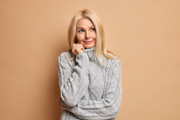 Good looking blonde mature european woman stands in thoughtful pose wears comfortable grey jumper concentrated aside ponders on making choice.