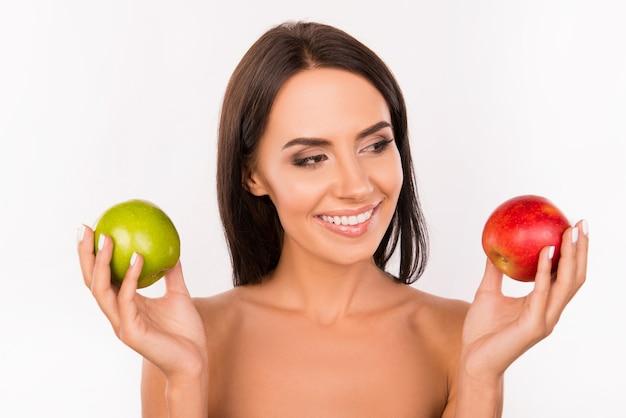 Красивая красивая женщина выбирает между зелеными и красными яблоками