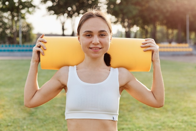 Good looking brunette female wearing white to holding yellow karemat on shoulders, looking smiling directly at camera, training outdoor in stadium in sunny day.