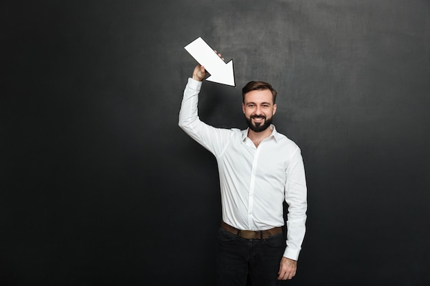Good-looking brunette man holding blank speech arrow pointer directing towards him over dark gray wall copy space