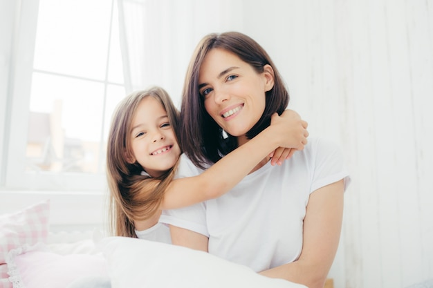Good looking brunette mother with gentle smile and her small daughter gives hug