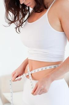 Good looking brunette woman measuring her belly