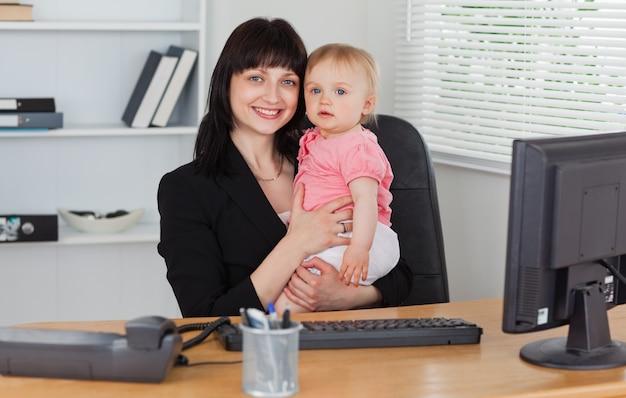 그녀의 무릎에 그녀의 아기를 잡고 포즈 좋은 찾고 갈색 머리 여자