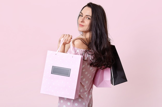 Good looking brunette woman stands sideways, holds shopping bags, returns from shopping mall in good mood, poses on pink. women and purchasing concept.