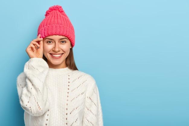 格好良いブルネットの若い女性は、顔の近くに手を保ち、心地よく微笑んで、帽子と白いニットのセーターを着て、良い感情を表現し、青いスタジオの壁に対してポーズをとる