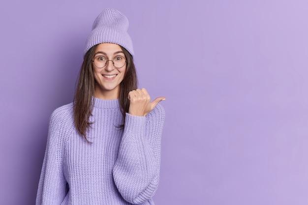 좋은 찾고 갈색 머리 젊은 여자는 복사 공간을 가리키는 보라색 모자 니트 스웨터와 둥근 안경을 착용 기쁜 포인트 엄지 손가락을 보인다