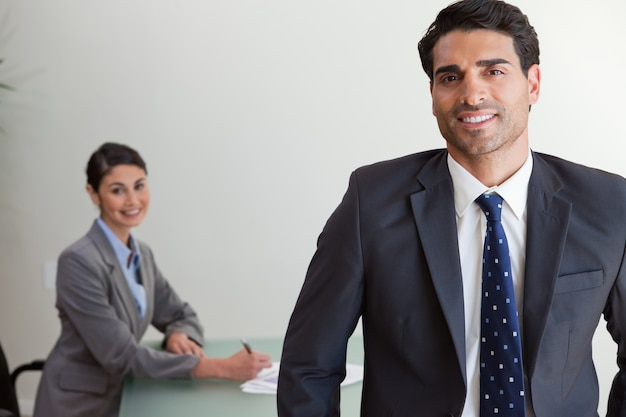 Good looking businessman posing while his colleague is working