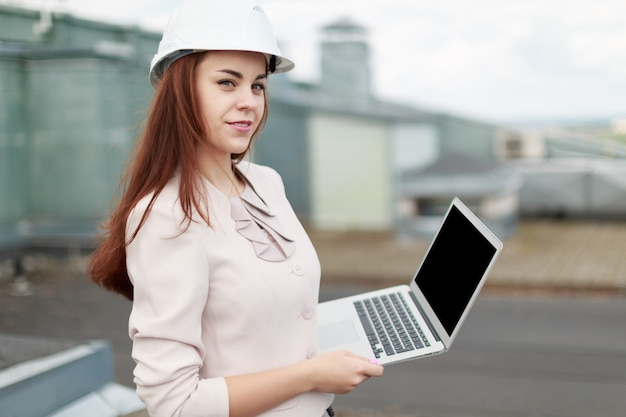 Good looking businesswoman in beige suit stand on the roof and hold laptop