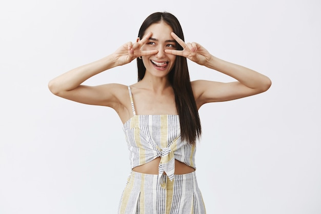 Good-looking carefree and playful cutie with dark hair in stylish matching top with shorts, showing victory signs over eyes, gazing left and smiling joyfully, sticking out tongue