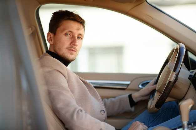 Good-looking caucasian driver dressed in beige jacket is sitting on the front seat of a new car and holding steering wheel