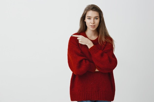 Good-looking caucasian female coworker in trendy red loose sweater, pointing left with index finger, explaining friend way how to get to great restaurant, suggesting grab coffee over gray wall