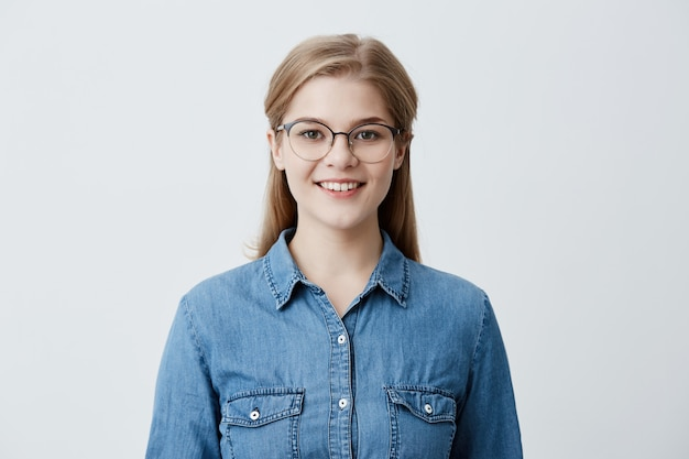 Good looking caucasian female with blonde straight hair, wearing glasses and denim shirt, smiles happily, has good mood after successful day at university, glad and pleased to pose