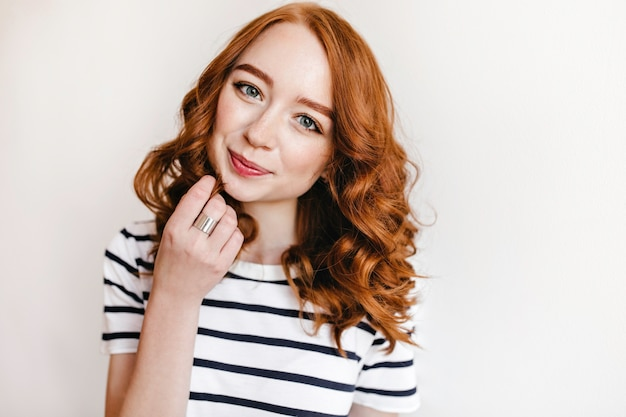 수줍은 미소로 포즈를 취하는 붉은 머리를 가진 잘 생긴 백인 소녀. 관심을 표현하는 매력적인 자신감 아가씨의 실내 사진.