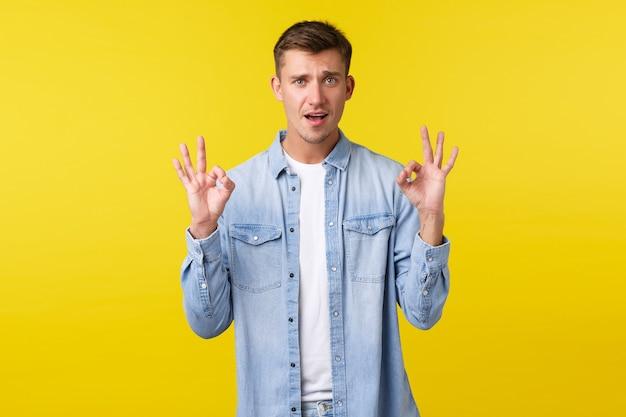 캐주얼한 옷을 입은 잘 생긴 카리스마 있는 게이 남자, 괜찮은 몸짓과 승인의 고개를 끄덕이고, 놀라운 제품을 평가하고, 훌륭한 서비스나 장소를 추천하고, 만족하고, 노란색 배경.