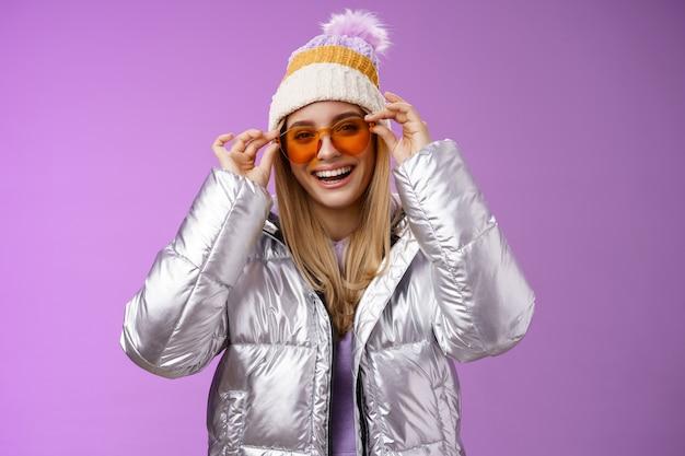 멋진 은색 빛나는 재킷 따뜻한 겨울 모자, 보라색 배경을 입고 기뻐 웃어 선글라스에 넣어 재미 휴가 여자 친구 데 잘 생긴 매력적인 행복 웃는 금발 여자 친구.