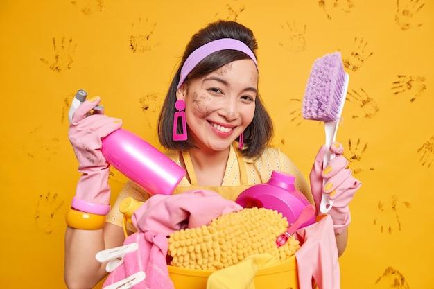Красиво выглядящая жизнерадостная азиатская женщина улыбается, счастливо держит кисть и моющее средство для стирки, занятая стиркой, носит защитные резиновые перчатки, имеет грязное лицо и позирует в помещении.