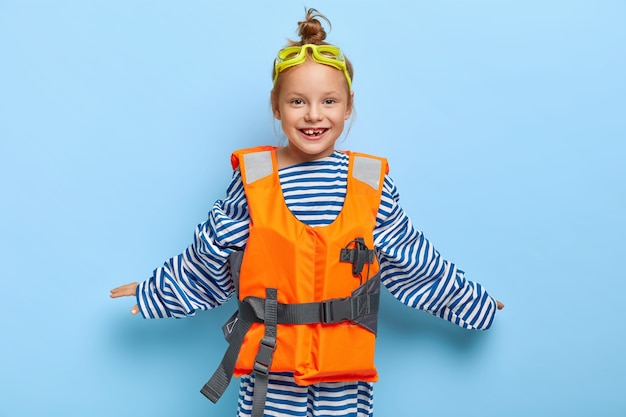 Good looking cheerful girl wears protective goggles, keeps hands spread sideways, wears fathers sailor sweater, orange lifejacket, tries to swim without parents help