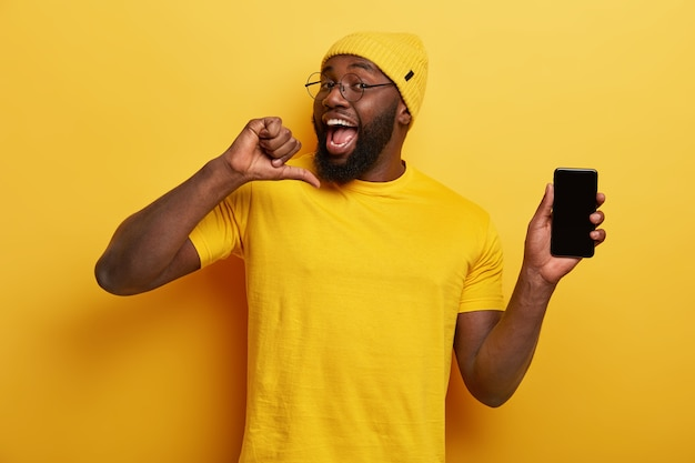 잘 생긴 쾌활한 남자가 자신을 가리키고 새로운 응용 프로그램을 개발하는 것을 자랑스럽게 생각하며 휴대 전화 화면을 보여줍니다.