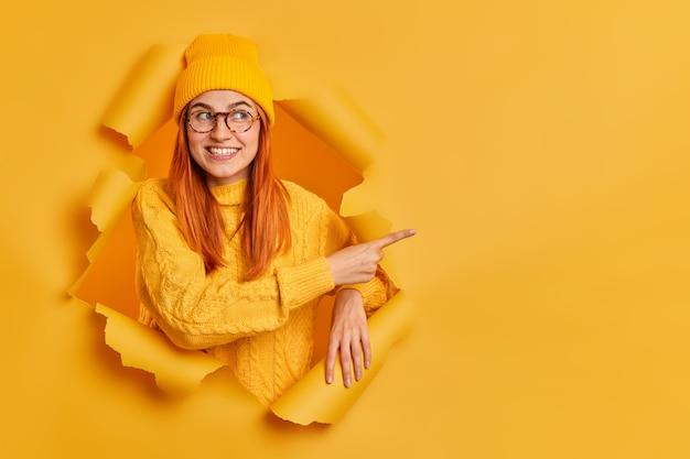 Симпатичная жизнерадостная миллениальная девушка с нежными улыбками указывает на копировальное пространство
