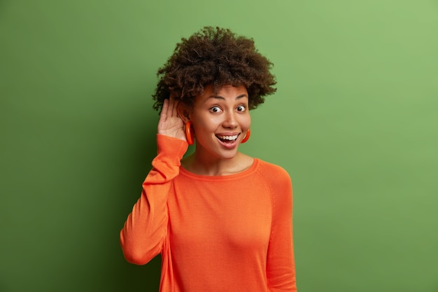Good looking cheerful woman with curly hair keeps hand near ear as tries to overhear interesting conversation, listens carefully coworkers who talk privately, being glad and curious, stands indoor