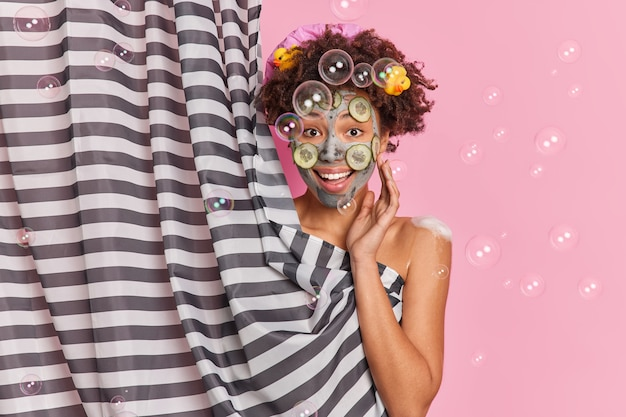 Good looking cheerful young afro american woman applies clay mask with cucumber slices on face hides her naked body takes care of body enjoys daily hygiene routine soap bubbles flying around