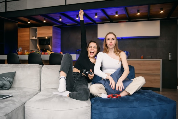 現代的なアパートのソファに座ってビデオゲームを楽しんでいる格好良い陽気な若い女性の友人