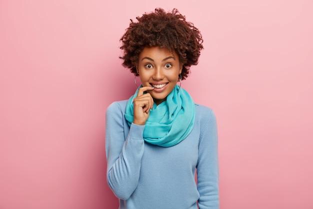 Симпатичная жизнерадостная молодая женщина с афро-прической, держит палец возле губ, выглядит позитивно, получает приятные новости, носит синий джемпер и шарф на шее, выражает положительные эмоции.