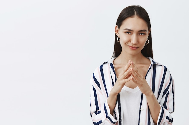Good-looking confident and tricky woman in striped blouse, holding fingers together and smirking, having some bad intention in mind, planning to commit crime