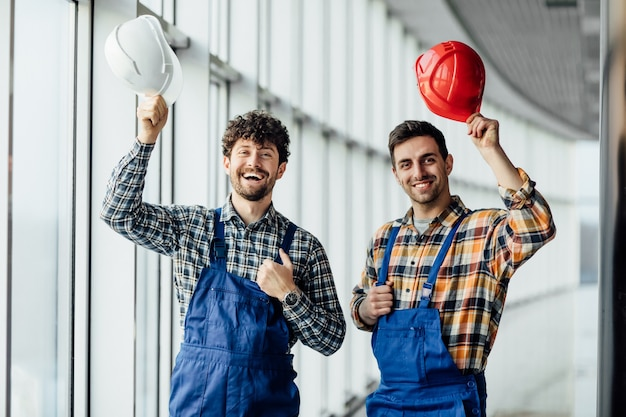 Good looking construction worker sharing with the experience with a colleague, holding helmet