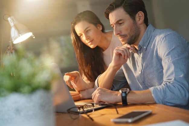 Good looking couple working on shared computer at home