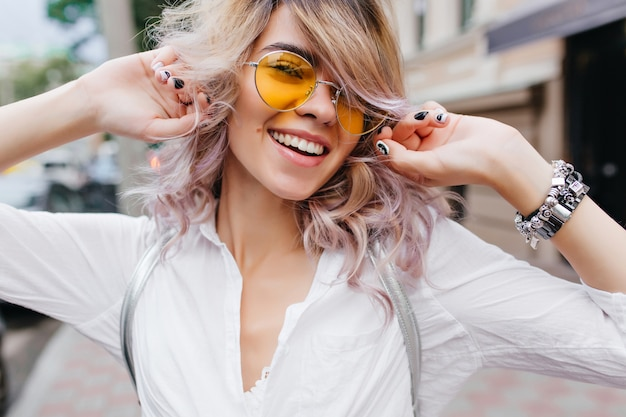 Good-looking curly girl with elegant haircut laughing while walking down the street in evening