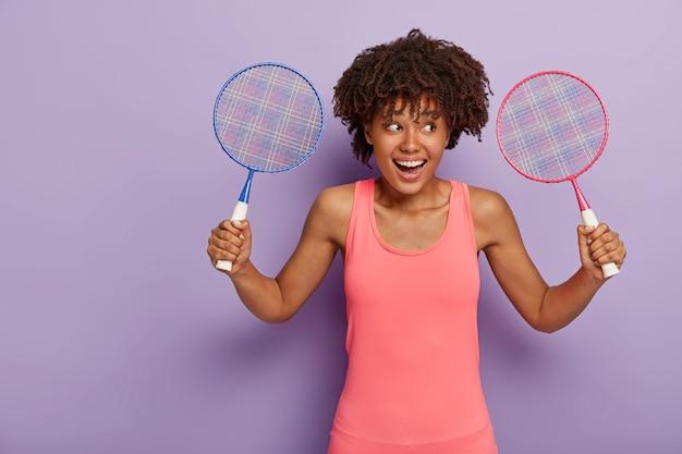 잘 생긴 곱슬 머리 젊은 여자가 두 개의 테니스 라켓을 들고 분홍색 조끼를 입고 친구와 좋아하는 게임을하고 싶어하며 긍정적으로 미소 짓습니다.