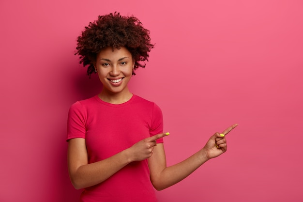 格好良い巻き毛の女性はさておき、素敵な製品をお勧めし、プロモーションの場所を示し、広く笑顔で、ピンクの壁に隔離されてこれを試してみてくださいと言います。広告用のスペースをコピーする