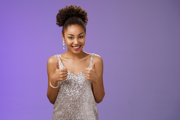 Good-looking daring african-american woman elegant silver evening dress agree help show thumbs up approval like gesture smiling broadly recommend great service think outfit suits her.