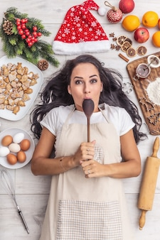 Good-looking dark haired cook biting the wooden spoon and laying on the ground and being surrounded by gingerbreads, eggs, flour on a wooden desk, christmas hat, dried oranges and baking forms