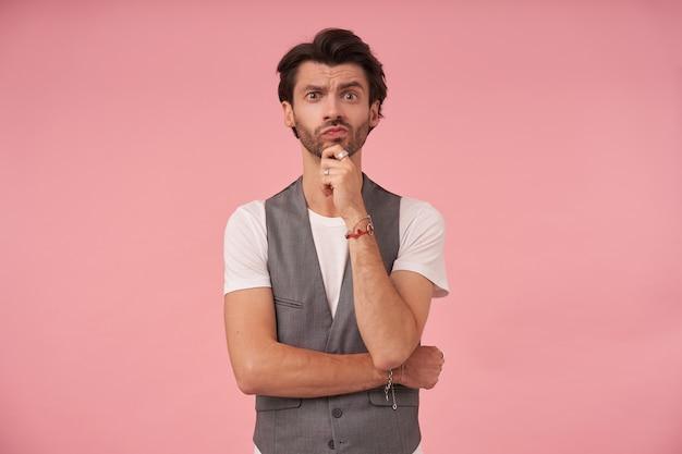 Bello maschio dai capelli scuri con la barba in piedi su sfondo rosa in gilet grigio e maglietta bianca, tenendo il mento con la mano e contraendo la fronte con le sopracciglia alzate