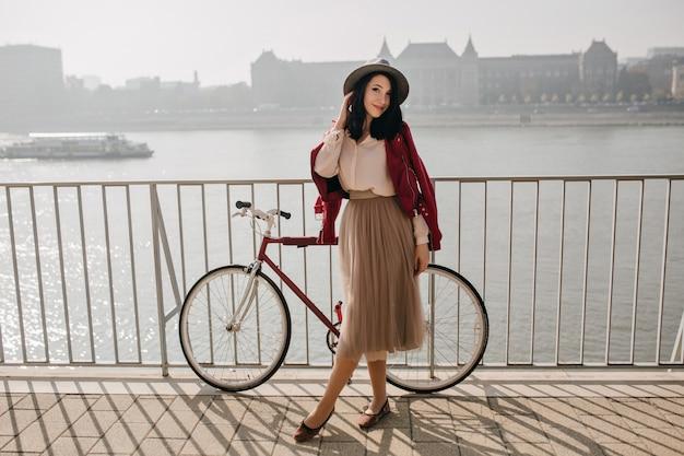 川の近くで時間を過ごすスカートのハンサムな黒髪の女性