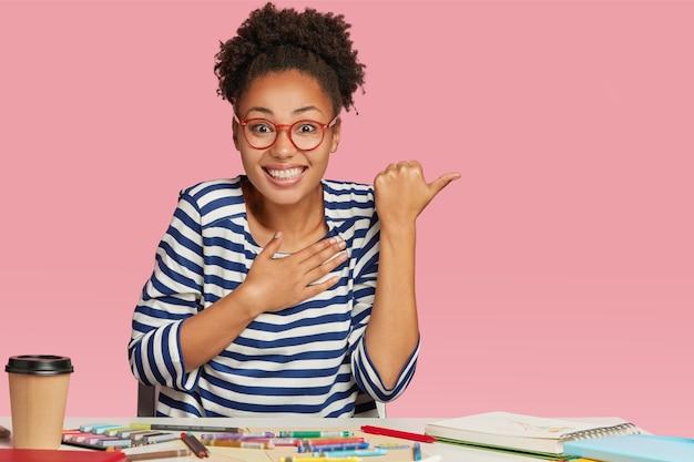 格好良い暗い肌の女の子は喜んで見え、前向きなことを信じることができず、創造的なプロジェクトを作成します
