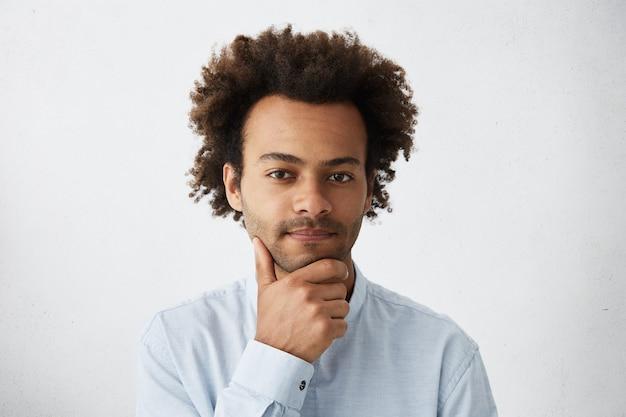 Симпатичный темнокожий мужчина с кудрявыми волосами и задумчивым выражением лица, держащий руку за подбородок