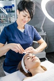 Красивый врач-косметолог делает на аппарате процедуру ультразвуковой чистки кожи лица.